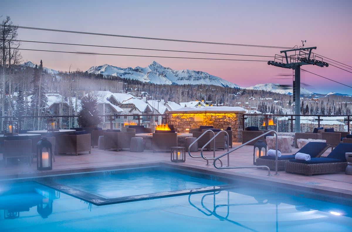 outdoor swimming pool at dusk, snowy mountains
